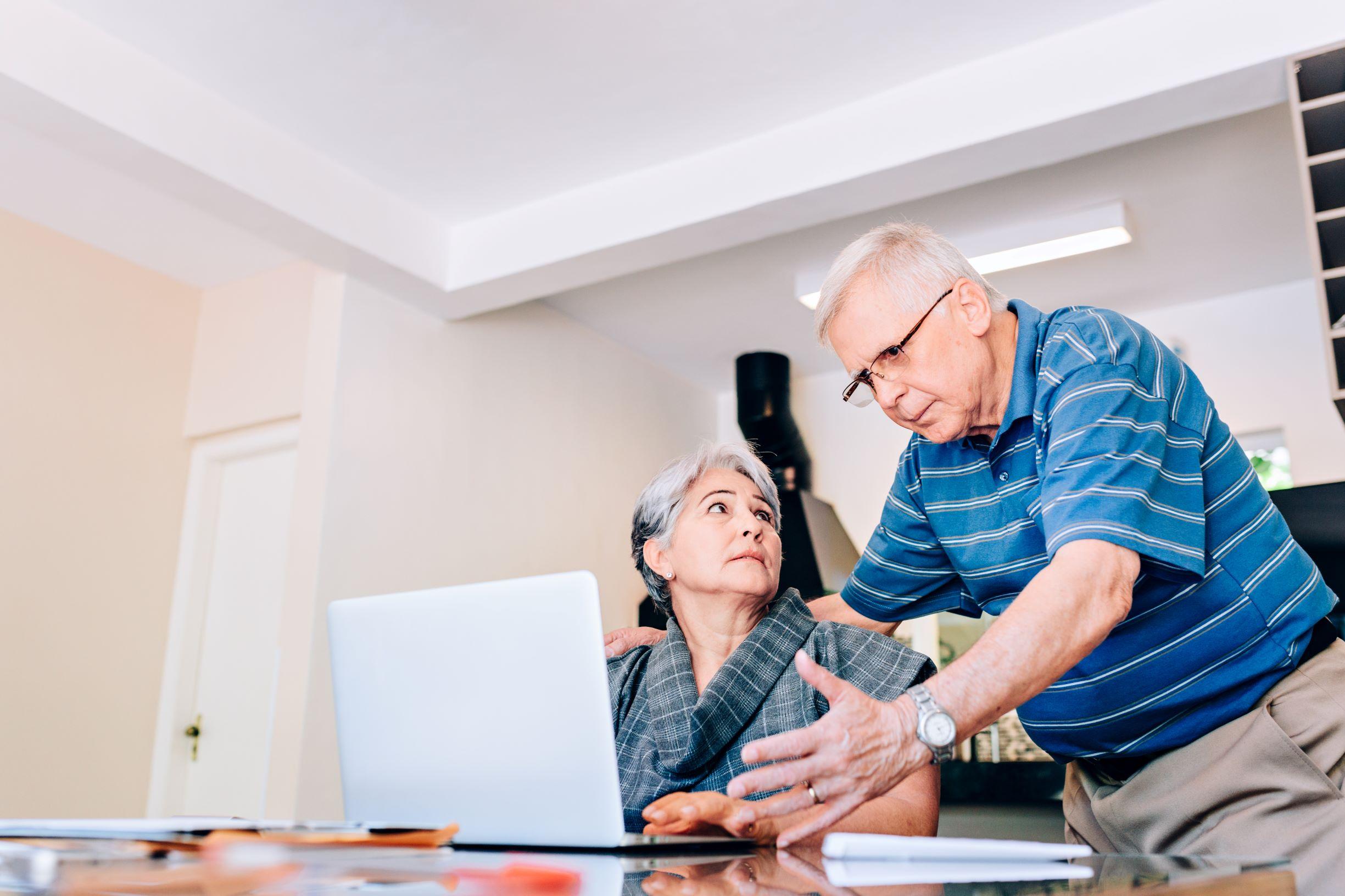 Older couple managing finances on a laptop