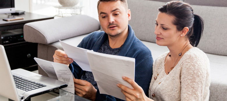 Couple looking at bills in front of laptop