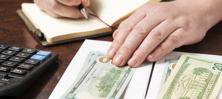 Person with hand on a stack of cash