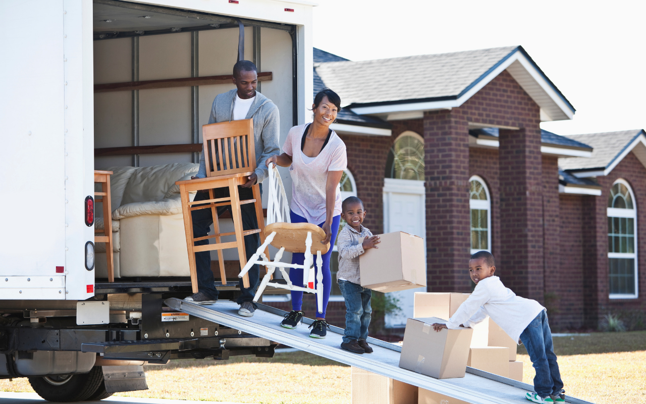 Family moving furniture into their new home