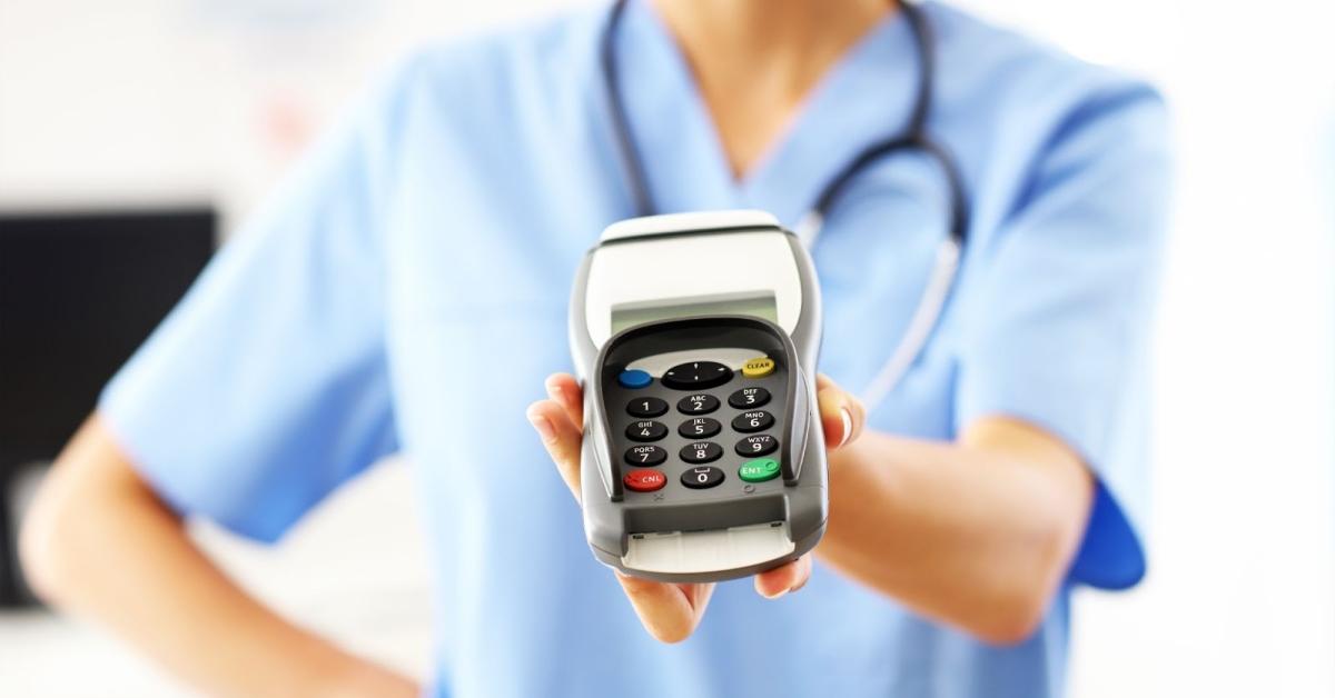 Medical professional holding credit card machine