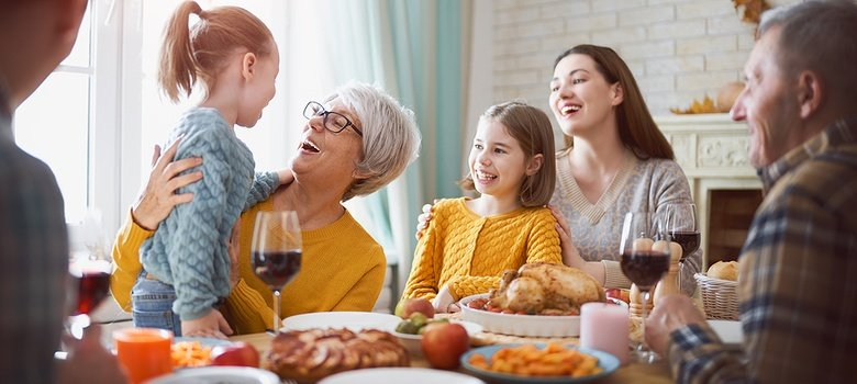 Family laughing carefree at dining room table