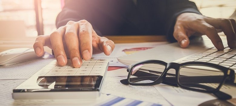 Person sitting at desk calculating bills with calculator