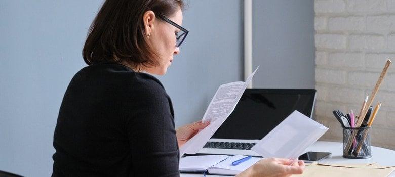 Woman sitting at desk reviewing bills