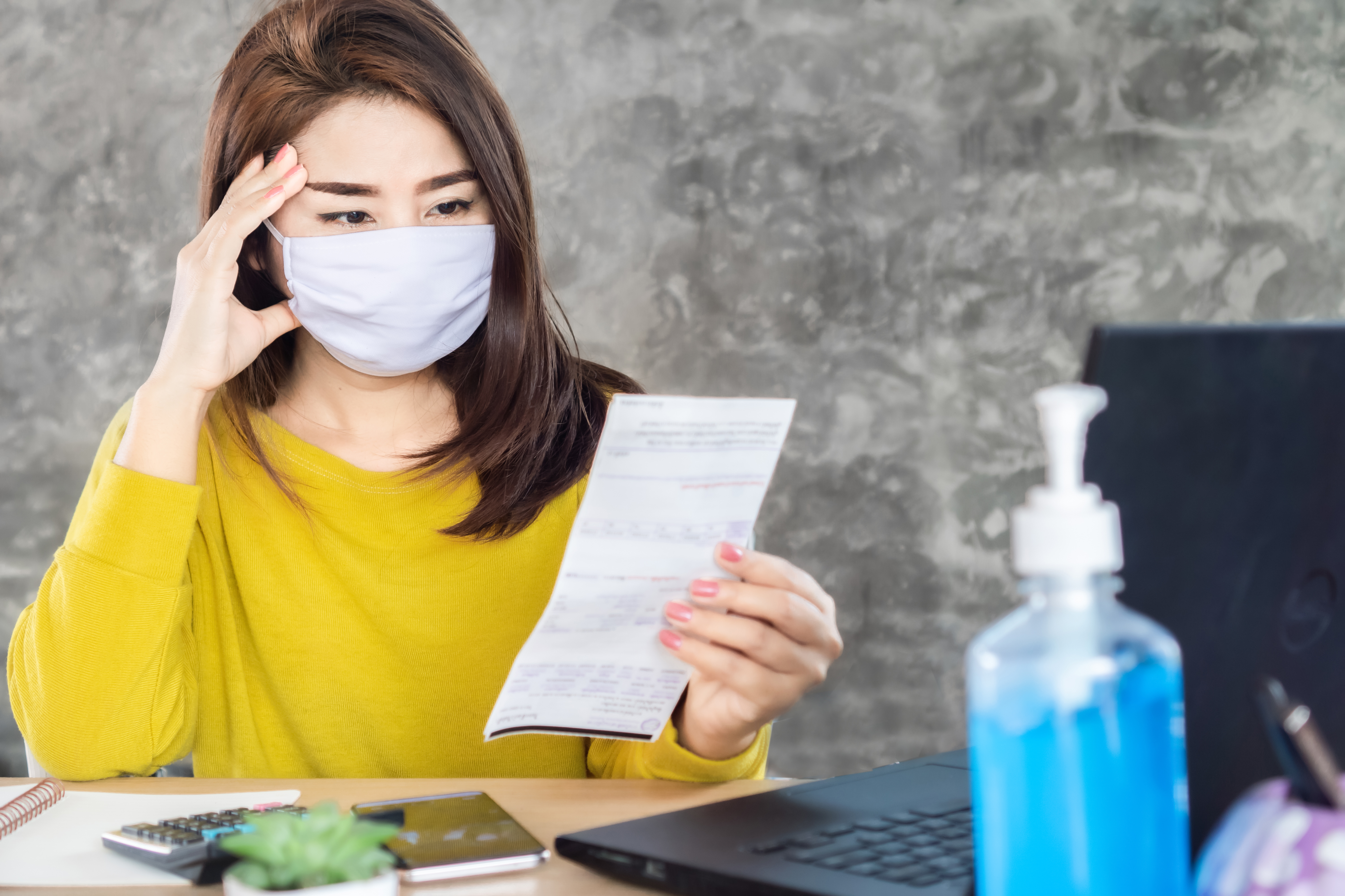 Woman holding a bill having financial problems during COVID-19 pandemic